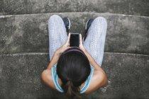 Joven mujer deportiva asiático con smartphone en escaleras - foto de stock