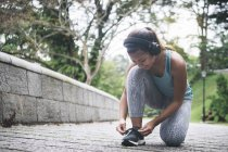Young asian sporty woman in headphones tying shoelaces in park - foto de stock