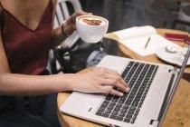 Image recadrée de la jeune femme en utilisant un ordinateur portable dans le café — Photo de stock