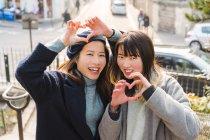 Молодые случайные азиатские девушки толкают сердца пальцами — стоковое фото