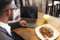 Hombre de negocios indio guapo usando el ordenador portátil y comer en la cafetería - foto de stock