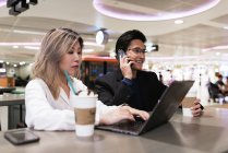 Successful business asian couple together working with laptop in airport — Stock Photo