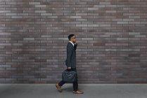 Красивый индийский бизнесмен ходит по улице с чемоданом — стоковое фото