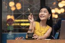 Heureuse jeune femme asiatique manger au café — Photo de stock