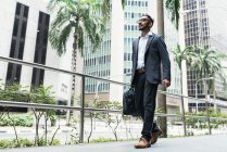 Handsome indian business man walking on street with suitcase — Stock Photo
