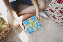 Imagen recortada de niño pequeño sosteniendo regalo de Navidad azul - foto de stock