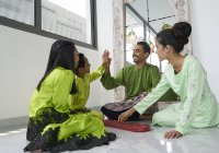 Young asian family celebrating Hari Raya together at home and playing traditional game — Stock Photo