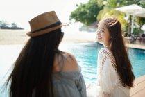 Hermosas mujeres asiáticas jóvenes relajantes junto a la piscina - foto de stock