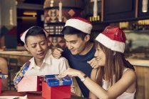 Happy young asian friends celebrating christmas together in cafe and sharing gifts — Stock Photo