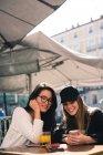 Двох красивих жіночих друзів за допомогою смартфона в кафе — стокове фото