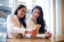Два красивих азіатських жінок за допомогою смартфона разом — стокове фото