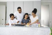 Giovane famiglia asiatica che celebra Hari Raya insieme a casa e cucina piatti tradizionali — Foto stock