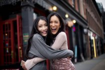 Deux asiatique fille amis câlins sur ville rue — Photo de stock