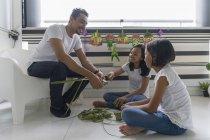 Feliz asiático familia celebrando hari raya en casa y preparando decoraciones - foto de stock