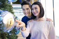 Young attractive asian couple together shopping in mall at christmas — Stock Photo