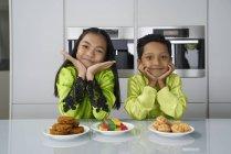 Молодые азиатские братья и сестры празднуют Хари Райя вместе дома — стоковое фото