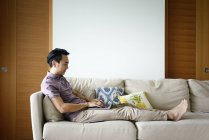 Side view of adult asian man using laptop at home — Stock Photo