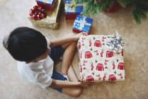 Happy boy celebrating Christmas and unpacking gifts at home — Stock Photo