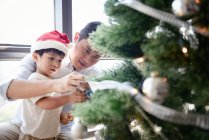 Happy asian family celebrating Christmas together at home and decorating fir tree — Stock Photo