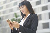 Giovane attraente asiatico businesswoman utilizzando smartphone in città — Foto stock