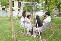Happy young asian family together taking photo on bench — Stock Photo