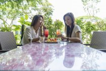 Two young ladies enjoying the fruits. — Stock Photo