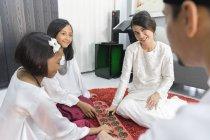 Happy asian family celebrating hari raya at home and playing traditional game — Stock Photo