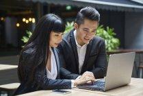 Casal jovem negócios asiáticos trabalhando em conjunto com o computador portátil — Fotografia de Stock