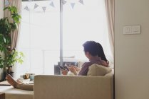 Adulto asiático pareja juntos en casa usando smartphones - foto de stock