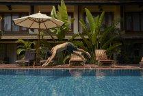 Jeune homme plongeant dans la piscine, vue latérale — Photo de stock