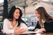 Two beautiful female friends looking at map in cafe — Stock Photo
