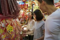 Young asian friends spending time together on traditional bazaar at Chinese New Year — Stock Photo