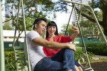 Young asian couple taking selfie on smartphone on swing — Stock Photo