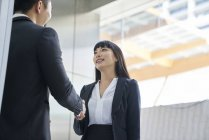 Young asian business couple shaking hands in modern office — Stock Photo
