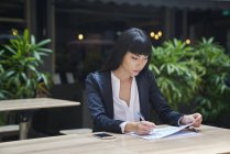 Young attractive asian businesswoman working in cafe — Stock Photo
