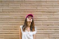 Молодая привлекательная азиатка в солнечных очках и розовой кепке — стоковое фото