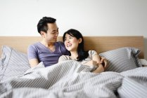 Adult asian couple together lying in bed at home — Stock Photo