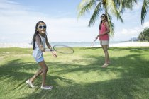 Young asian mother with cute daughter playing in badminton outdoors — Stock Photo