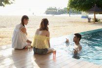 Young attractive asian friends spending time in pool — Stock Photo