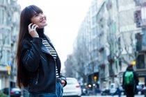 Jeune attrayant asiatique femme en ville en utilisant smartphone — Photo de stock