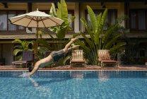 Молодой человек ныряет в бассейн, вид сбоку — стоковое фото