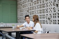 Giovane attraente asiatico coppia insieme seduta in caffè — Foto stock