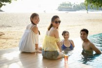Beautiful young asian friend relaxing near pool — Stock Photo