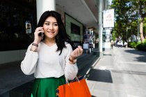 Young woman using her phone along Orchard Road. — Stock Photo