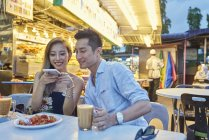 Happy young asian couple sitting together in street cafe — Stock Photo