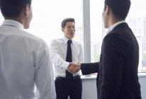 Jeunes hommes d'affaires asiatiques serrant la main au bureau moderne — Photo de stock