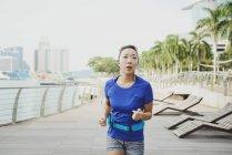 Giovane donna asiatica sportiva in esecuzione al parco — Foto stock