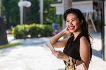 Smiling asian woman with shopping bags using smartphone — Stock Photo