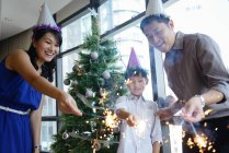 Happy asian family celebrating Christmas together at home with sparklers — Stock Photo