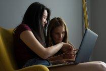Chinesin mit Freund und Laptop amüsiert sich im gelben Sessel. — Stockfoto